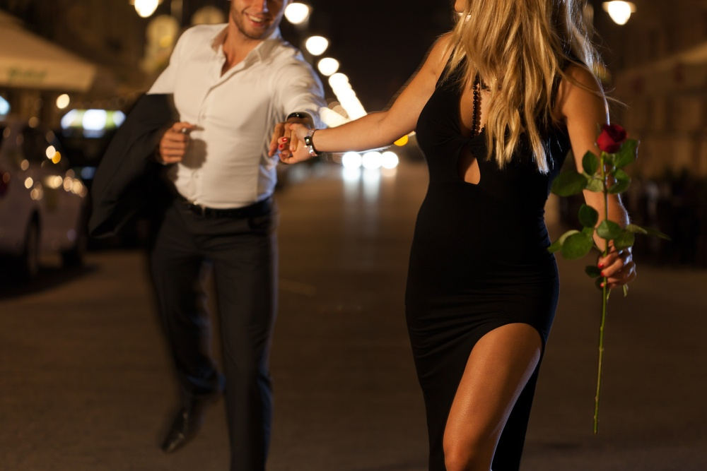 An elegant couple holding hands when running on a date at night